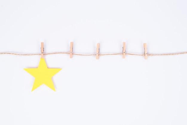 Concetto di valutazione. la foto di una piccola stella che appende sul filo con il posto per cinque stelle ha isolato il fondo bianco con lo spazio vuoto