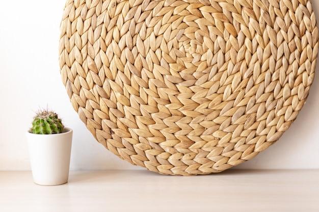 Cesto in rattan decorazione da parete in stile bohémien scandinavo. mensola con cactus. decorazione della stanza alla moda ecologica. copia cornice spaziale