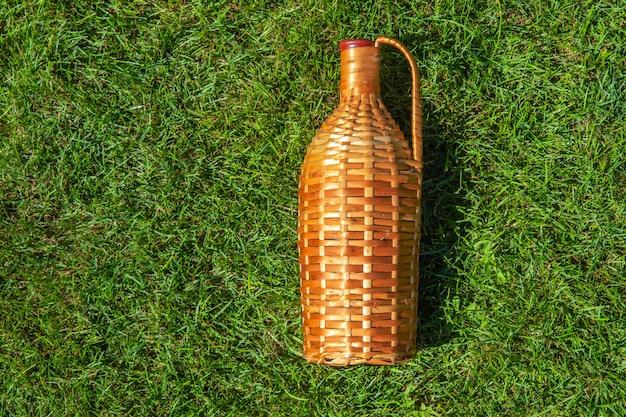 Bottiglia di vino del rattan che mette su prato inglese dell'erba verde, concetto del nic del pic