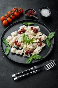 Ravioli di pasta con salsa di crema di funghi e formaggio - stile alimentare italiano impostato con basilico parmigiano e pomodoro sulla piastra nera, su sfondo nero