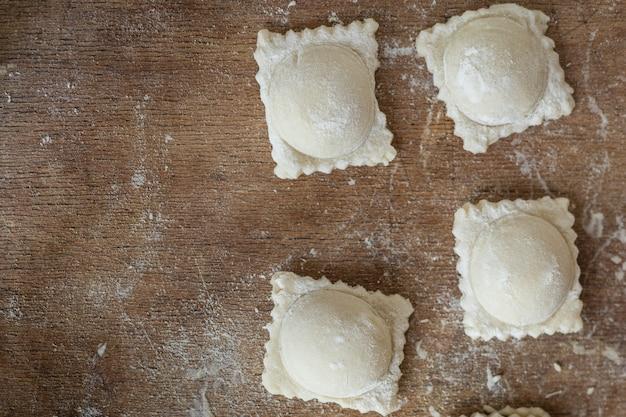 Ravioli pasta cruda ripieno di gnocchi quadrati sul tavolo pasto sano spazio copia sfondo alimentare