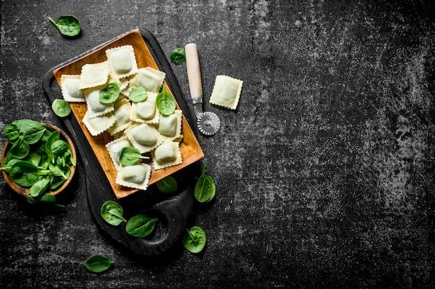 Ravioli crudi su un piatto con spinaci sul tavolo rustico scuro.