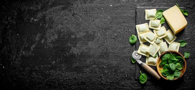 Ravioli crudi con carne di manzo su una tavola di pietra sul tavolo rustico nero.