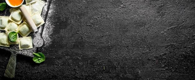 Ravioli crudi con carne su un tagliere. sulla tavola rustica nera