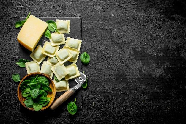 Ravioli a crudo con foglie di parmigiano e spinaci. sul nero rustico