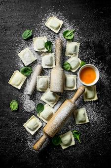 Ravioli crudi con salsa e foglie di spinaci. sul nero rustico