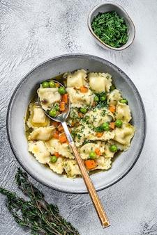 Ravioli zuppa di gnocchi di pasta in una ciotola con verdure. sfondo bianco. vista dall'alto.