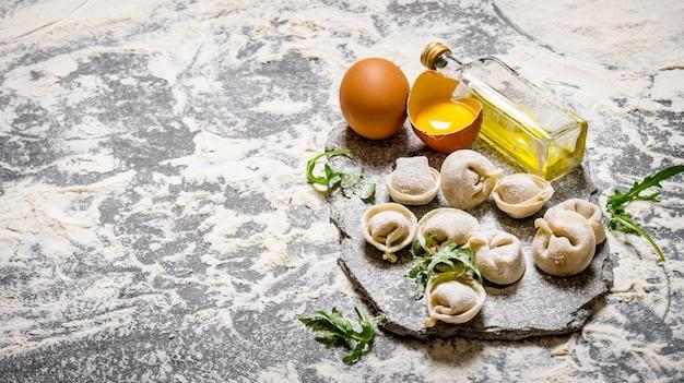 Ravioli con uova, olio d'oliva ed erbe aromatiche. sul tavolo di pietra con farina.