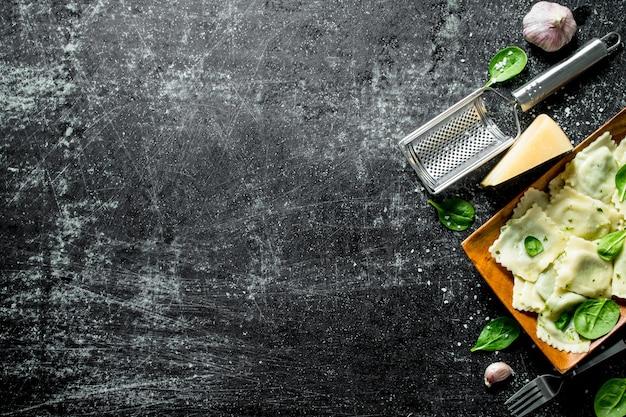 Ravioli con aglio, formaggio e spinaci. sul tavolo rustico scuro