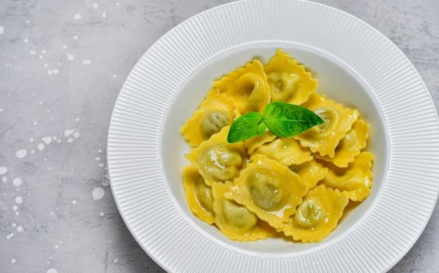 Ravioli con ricotta e spinaci in un piatto bianco su un tavolo di pietra grigia. ricetta di pasta italiana, pranzo gourmet. vista dall'alto