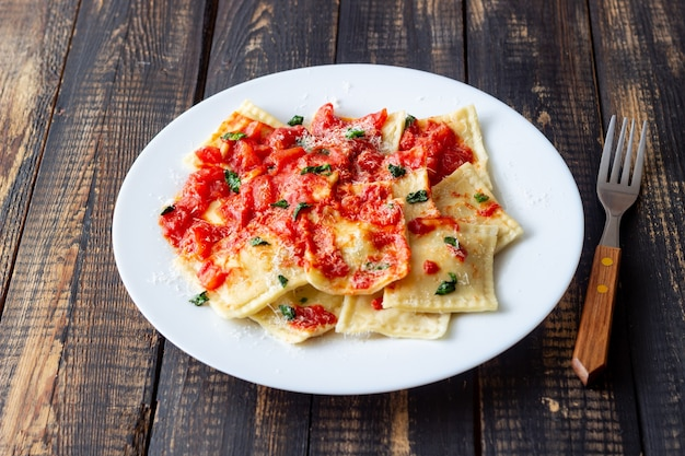 Ravioli con salsa di pomodoro, spinaci e parmigiano. mangiare sano. cibo vegetariano. cucina italiana.