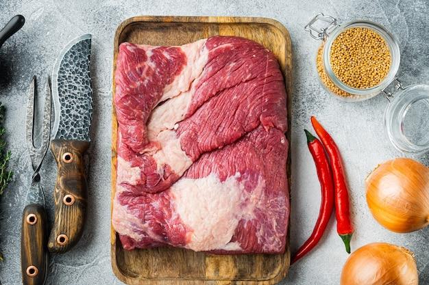 Pancia di manzo crudo, set di carne di petto di manzo, con ingredienti per fumare facendo barbecue, pastrami, cura, su pietra grigia