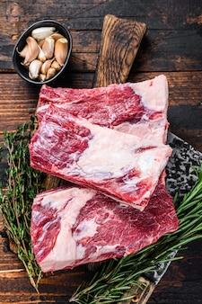 Carne di costolette di vitello crudo su un tagliere da macellaio con mannaia