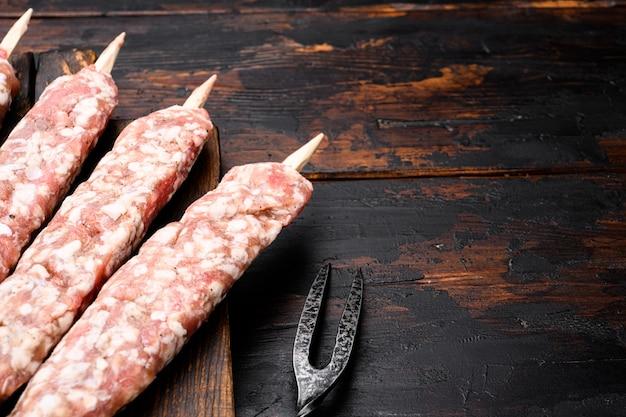 Set di salsicce di spiedini di carne di manzo e agnello crudi, su vecchio fondo di legno scuro della tavola, con spazio di copia per il testo