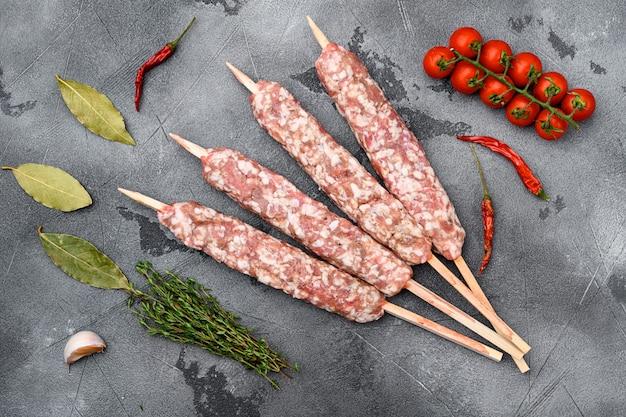 Set di salsicce crude di spiedini di carne di manzo e agnello, con ingredienti alla griglia, su sfondo grigio tavolo in pietra, vista dall'alto piatta