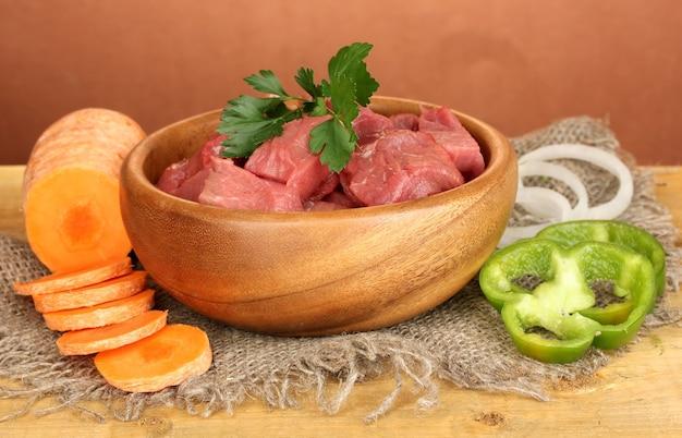 Carne di manzo cruda in ciotola con le verdure sulla tavola di legno su fondo marrone