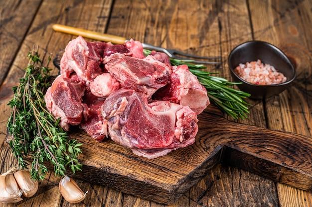 Carne di manzo cruda tagliata a dadini per stufato con osso in legno