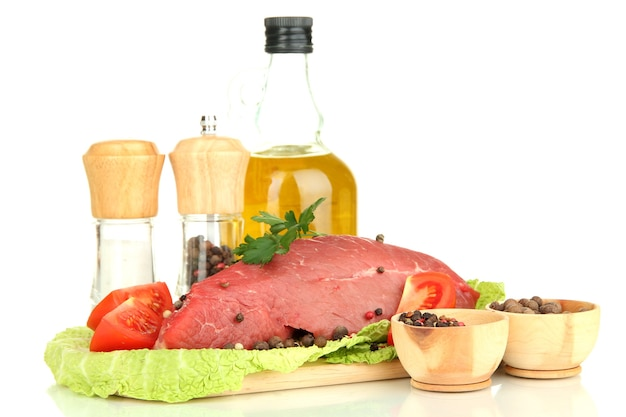Carne di manzo cruda marinata con erbe, spezie e olio da cucina isolato su bianco