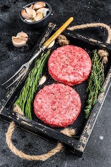 Tortini di carne di manzo cruda per hamburger da carne macinata ed erbe su una tavola di legno