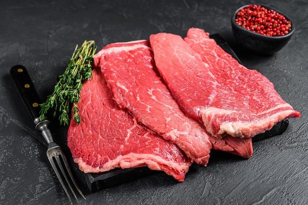 Bistecca rotonda di carne di manzo cruda su una tavola di marmo.