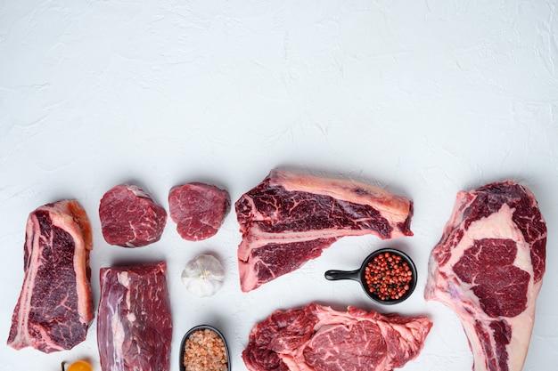 Set di bistecche di carne di manzo crudo, tomahawk, t bone, club steak, rib eye e tagli di filetto, su sfondo di pietra bianca, vista dall'alto piatta, con copia spazio per il testo