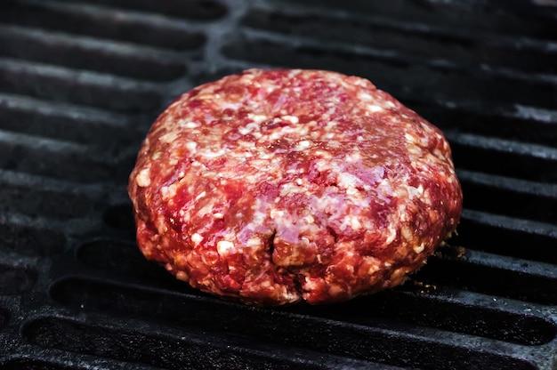 Patty di manzo crudo per hamburger sulla griglia calda nera. tortino crudo di carne macinata fresca. il processo di preparazione dei condimenti per un burger