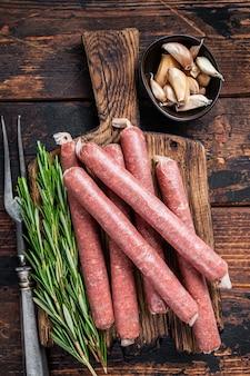 Carne di manzo crudo e salsiccia di maiale sul vecchio tagliere con forchetta di carne d'epoca. fondo in legno scuro. vista dall'alto.
