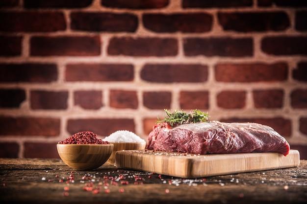 Bistecca di manzo cruda con sale pepe ed erbe aromatiche su tavola da macellaio in legno.