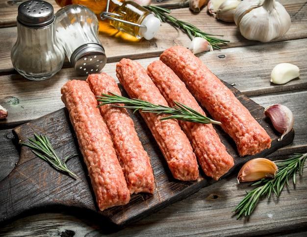 Salsicce di manzo crude con erbe e spezie su un tavolo rustico.