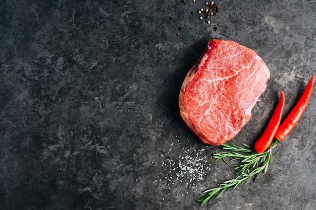 Bistecca di manzo cruda su sfondo nero con peperoncino rosmarino e spezie copia spazio
