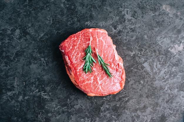 Bistecca di manzo cruda su sfondo nero con rosmarino