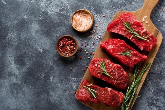 Bistecca di manzo cruda con spezie, cipolle e rosmarino su sfondo scuro di ardesia o cemento. vista dall'alto.