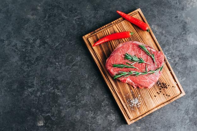 Bistecca di manzo crudo su tavola di legno e sfondo nero con peperoncino rosmarino e spezie copia spazio