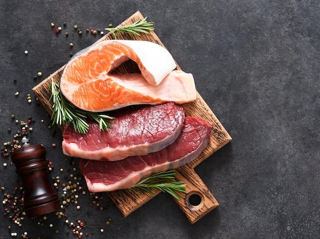 Bistecche di manzo crude e bistecca di salmone e rosmarino su una tavola su uno sfondo concreto.