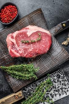Roastbeef di manzo crudo sulla bistecca di carne con l'osso. fondo nero. vista dall'alto.