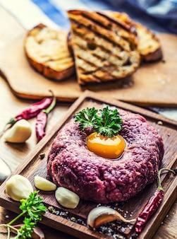 Manzo crudo. tartare di bistecca saporita. tartare di bistecca classica su tavola di legno. ingredienti: carne cruda di manzo sale pepe uovo aglio peperoncino erbe aromatiche e crostini di pane