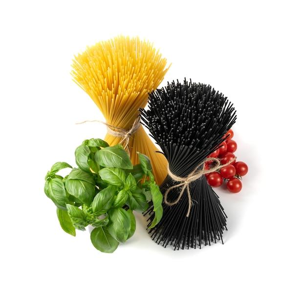 Pasta nera cruda e mazzo di spaghetti giallo isolato su priorità bassa bianca