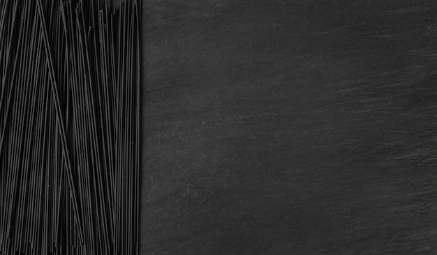 Mockup di spaghetti crudi neri su sfondo scuro