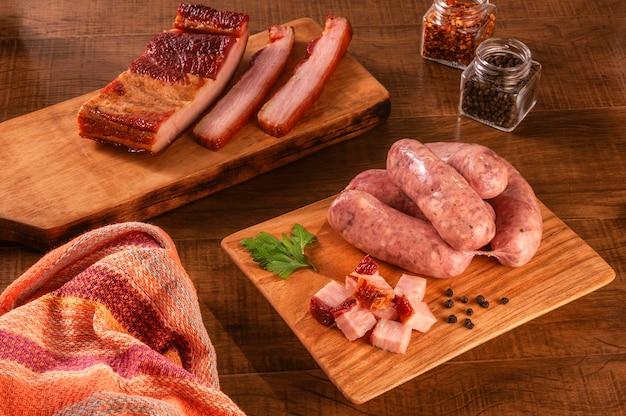 Salsicce di pancetta brasiliana crude sulla tavola di legno con cubetti di pancetta fresca e spezie