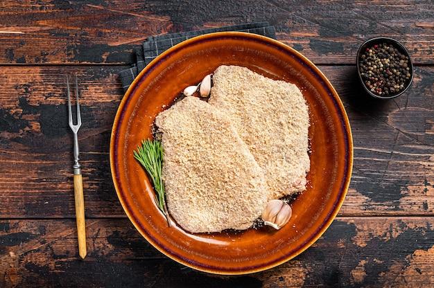 Cotoletta alla milanese impanata cruda su un piatto rustico con erbe aromatiche. fondo in legno scuro. vista dall'alto.
