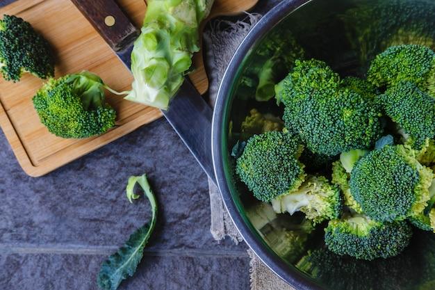 Broccoli crudi tagliati in un tagliere di legno
