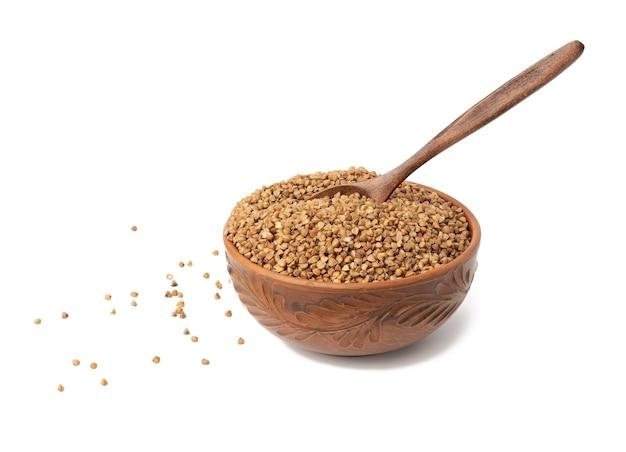 Chicchi di grano saraceno crudi in piatto di ceramica marrone e cucchiaio di legno, cereali isolati