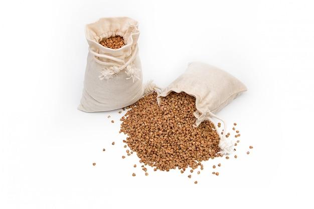 Grano saraceno crudo in un sacco di lino o di iuta su uno spazio bianco.