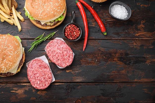 Hamburger crudo che cucina un hamburger con carne su fondo di legno scuro con spazio per testo.