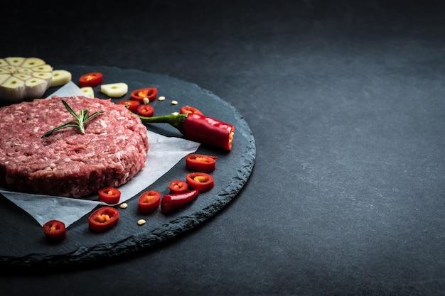Cotoletta cruda dell'hamburger dalla carne di manzo con aglio e rosmarino su fondo nero con lo spazio della copia
