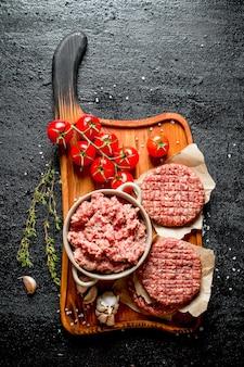 Hamburger crudi e carne macinata con pomodori, spicchi d'aglio e timo. su fondo rustico