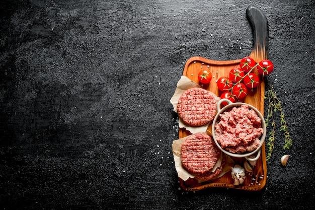 Hamburger crudi e carne macinata con pomodori, spicchi d'aglio e timo. su superficie rustica