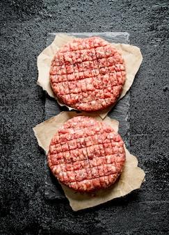 Hamburger crudi su carta. su sfondo nero rustico