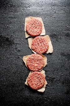 Hamburger crudi su carta. sulla tavola rustica nera