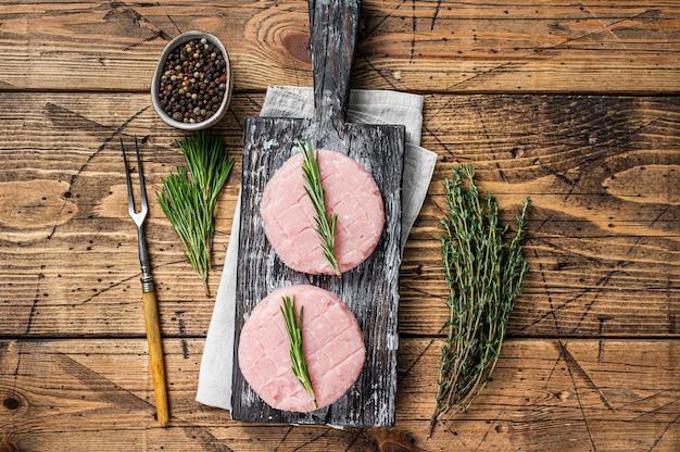 Tortino di hamburger crudo di carne di pollo e tacchino biologico con timo e rosmarino. fondo in legno. vista dall'alto.